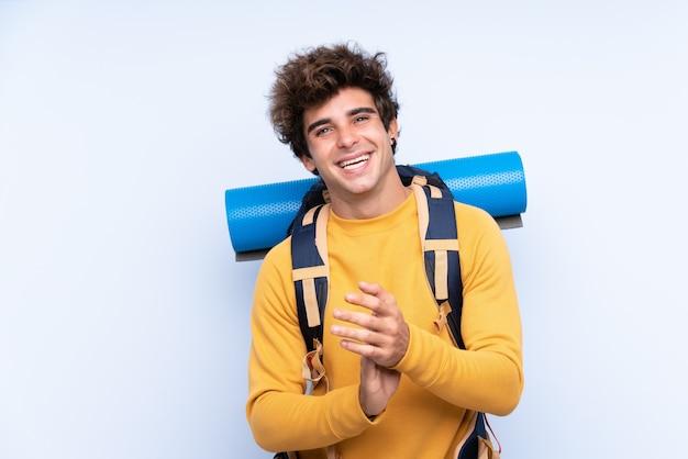 Junger bergsteigermann mit einem großen rucksack über lokalisiertem blauem wandapplaudieren Premium Fotos