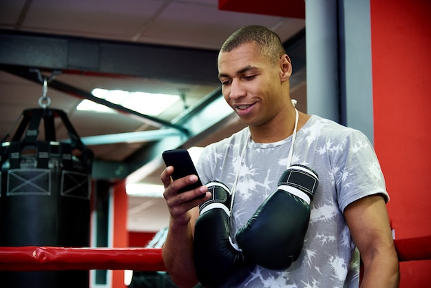 Junger berufsboxer mit einem telefon im ring auf hintergrund der turnhalle mit taschen. Premium Fotos