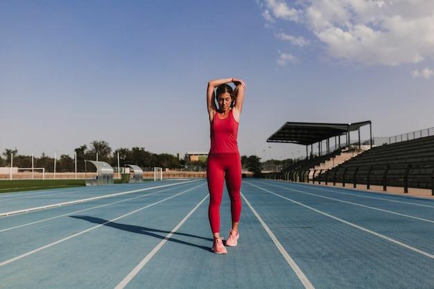 Junger blonder eignungsfrauenläufer, der arme auf blauer bahn des stadions bei sonnenuntergang ausdehnt. sport und gesundes lebensstilkonzept Premium Fotos