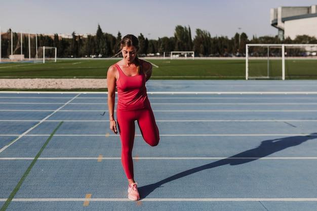 Junger blonder eignungsfrauenläufer, der beine auf blauer bahn des stadions bei sonnenuntergang ausdehnt. sport und gesundes lebensstilkonzept Premium Fotos