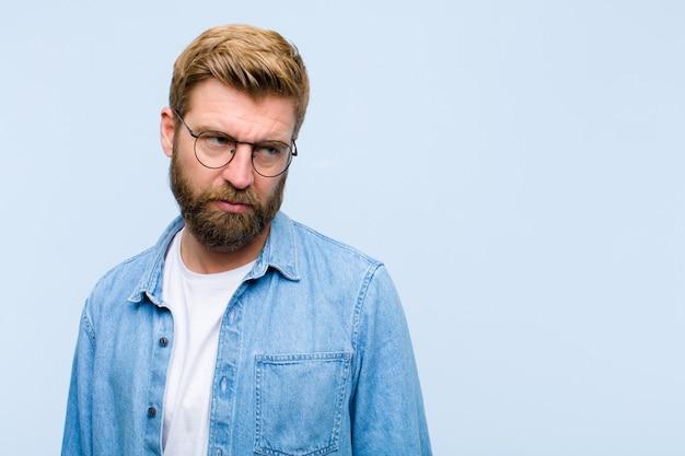 Junger blonder erwachsener mann, der traurig, verärgert oder verärgert sich fühlt und zur seite mit einer negativen haltung schaut und in der uneinigkeit die stirn runzelt Premium Fotos