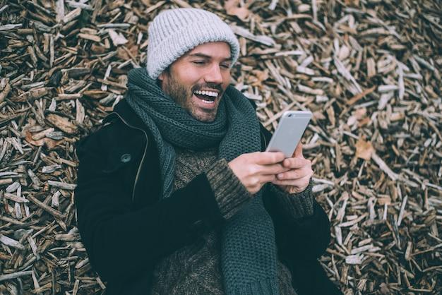 Junger blonder mann am handy, der auf frieden des holzes nahe dem königlichen palast in madrid während des winters liegt Premium Fotos