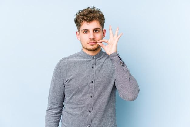 Junger blonder mann mit lockigem haar, dessen finger auf den lippen ein geheimnis bewahren Premium Fotos
