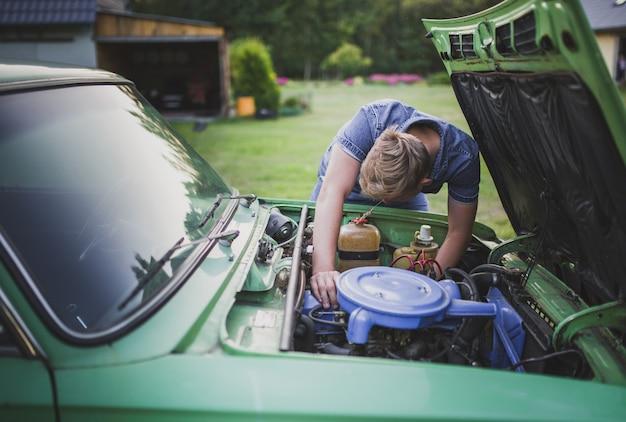 Junger blonder mann müde und enttäuscht, ein altes auto zu reparieren Kostenlose Fotos