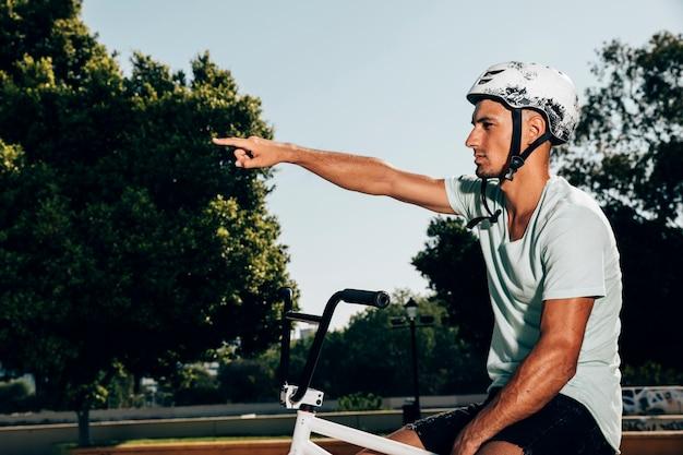 Junger bmx mitfahrer auf seinem fahrrad mittleren schuss unterstreichend Kostenlose Fotos