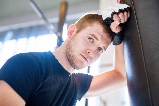 Junger boxer, der auf sandsack sich lehnt Kostenlose Fotos