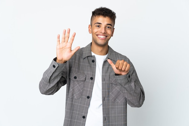 Junger brasilianischer mann lokalisiert auf weißer wand, die sechs mit den fingern zählt Premium Fotos