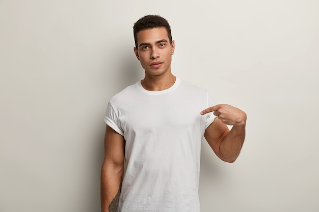 Junger brunetmann, der weißes t-shirt trägt Kostenlose Fotos