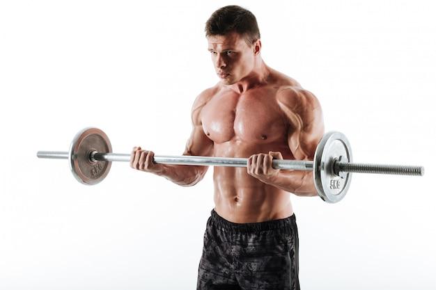 Junger brutaler muskulöser mann, der mit langhantel trainiert und beiseite schaut Kostenlose Fotos