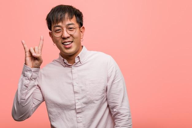 Junger chinesischer mann, der eine felsengeste tut Premium Fotos