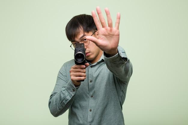 Junger chinesischer mann, der eine weinlese einsetzt hand in front hält Premium Fotos