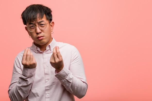 Junger chinesischer mann, der einen gestenbedarf tut Premium Fotos