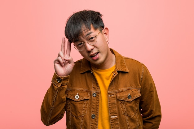 Junger chinesischer mann, der einen jackenspaß trägt und glücklich ist, eine geste des sieges tuend Premium Fotos
