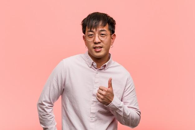 Junger chinesischer mann, der oben daumen lächelt und anhebt Premium Fotos