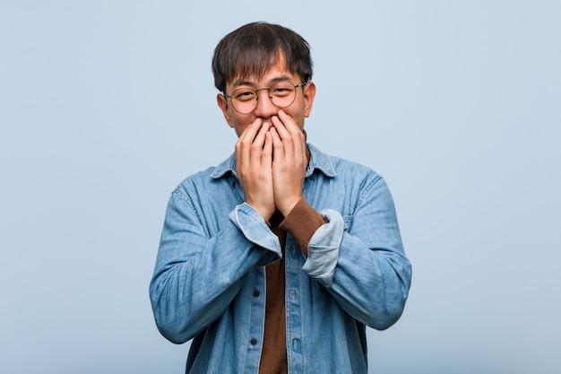Junger chinesischer mann, der über etwas, mund mit den händen bedeckend lacht Premium Fotos