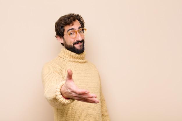 Junger cooler mann, der lächelt, sie begrüßt und einen handschlag anbietet, um einen erfolgreichen deal abzuschließen Premium Fotos