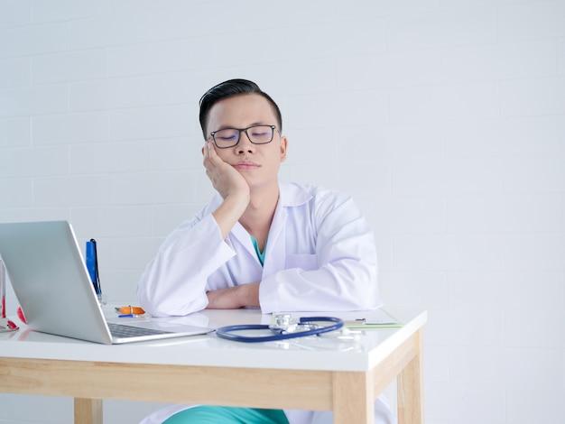 Junger doktor, der auf seiner hand im büro sich lehnt Premium Fotos
