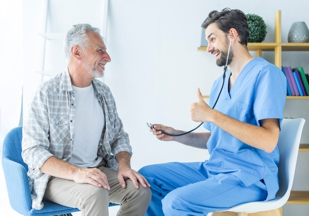 Junger doktor, der dem älteren patienten daumen-oben gestikuliert Kostenlose Fotos