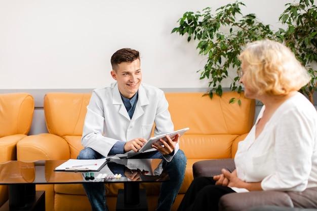 Junger doktor, der eine tablette hält und patienten betrachtet Kostenlose Fotos