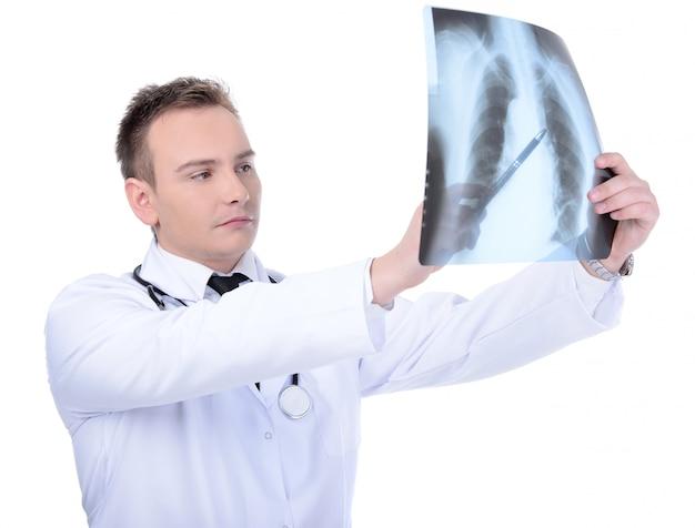 Junger doktor, der zum röntgenstrahl, getrennt schaut Premium Fotos