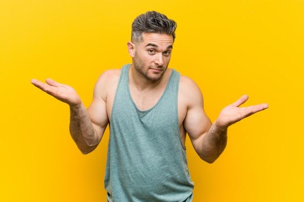 Junger eignungsmann gegen ein gelb, das schultern in fragender geste bezweifelt und zuckt. Premium Fotos