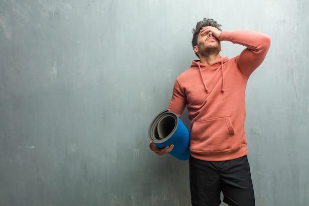 Junger eignungsmann gegen eine grunge wand frustriert und verzweifelt, verärgert und traurig mit den händen auf dem kopf. Premium Fotos