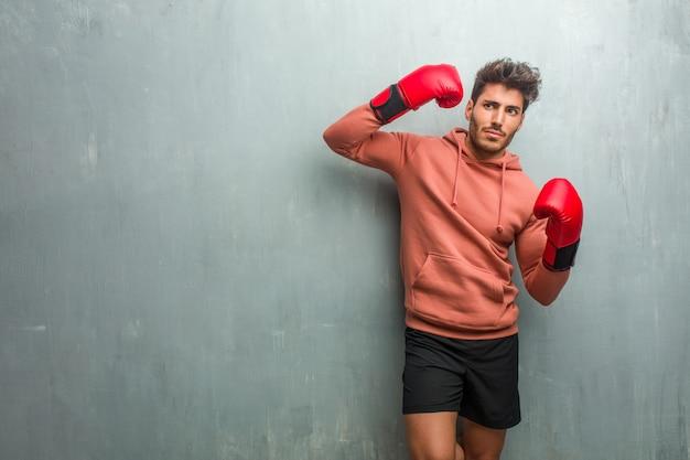 Junger eignungsmann gegen eine schmutzwand, die eine selbstmordgeste macht, traurig und erschrocken glaubt, ein gewehr mit den fingern bildend. Premium Fotos