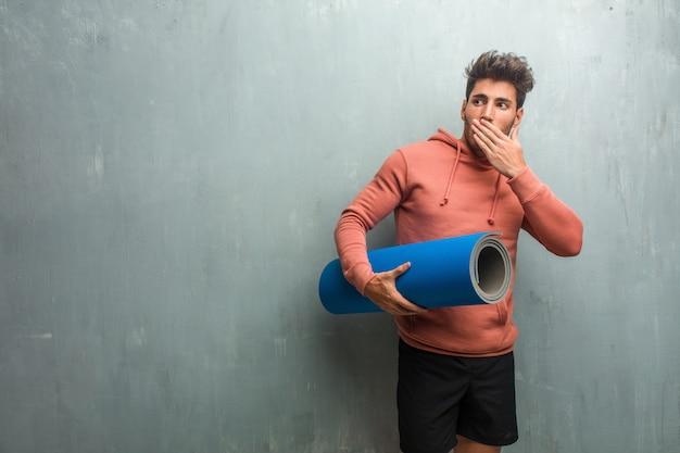 Junger eignungsmann gegen einen schmutzwandbedeckungsmund, symbol der ruhe und unterdrückung Premium Fotos