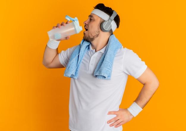 Junger eignungsmann im weißen hemd mit dem stirnband und dem handtuch um hals, der flasche trinkwasser nach dem training steht über orange hintergrund hält Kostenlose Fotos