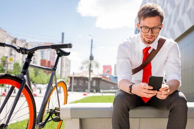 Junger eleganter geschäftsmann, der online-video oder lesende nachricht im smartphone beim sitzen auf bank mit seinem fahrrad in der nähe betrachtet Premium Fotos