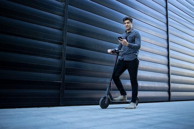 Junger eleganter mann, der mit elektroroller geht und smartphone verwendet Kostenlose Fotos