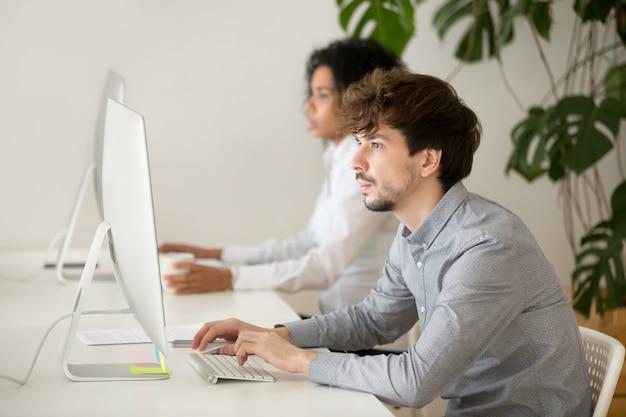 Junger ernster angestellter konzentrierte sich auf computerarbeit im gemischtrassigen büro Kostenlose Fotos