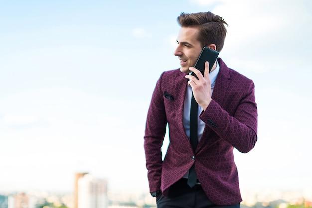 Junger ernster geschäftsmann im roten anzug und hemd mit bindung stehen auf dem dach und sprechen am telefon Premium Fotos