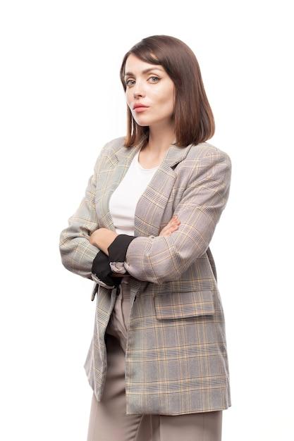 Junger ernsthafter lehrer oder geschäftsfrau, die arme durch brust kreuzen, während sie isoliert stehen Premium Fotos