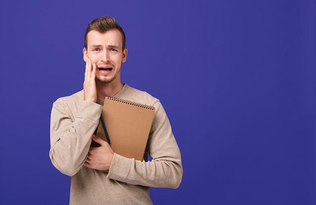 Junger erschrockener student hält seine hand am mund, öffnet seinen mund und schreit Premium Fotos