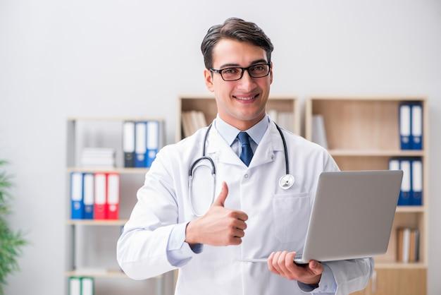 Junger erwachsener doktor mit laptop-computer Premium Fotos