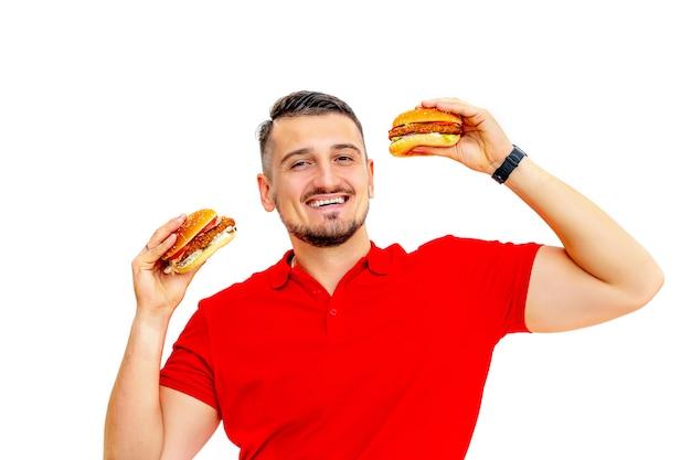 Junger erwachsener mann mit bart, der köstliche frische große burger auf weißem hintergrund isst Premium Fotos