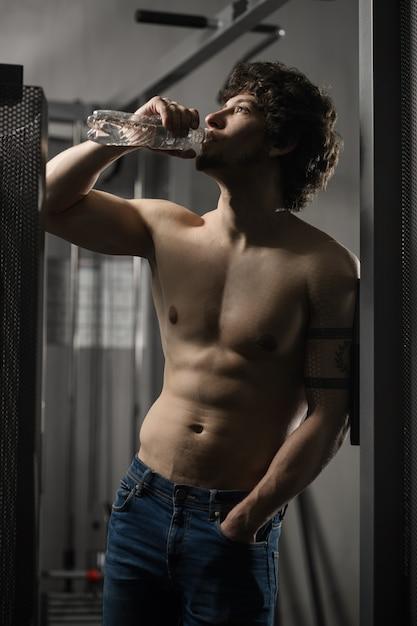 Junger erwachsener mann trinkt flasche wasser in der turnhalle Premium Fotos