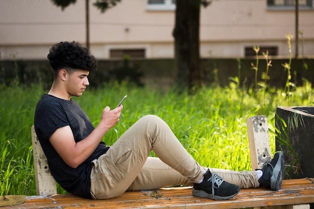 Junger ethnischer mann, der auf bank sitzt und smartphone verwendet Kostenlose Fotos