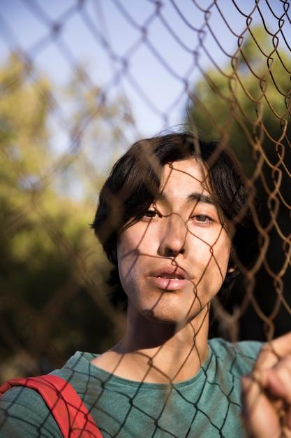 Junger ethnischer mann, der kamera durch drahtzaun betrachtet Kostenlose Fotos