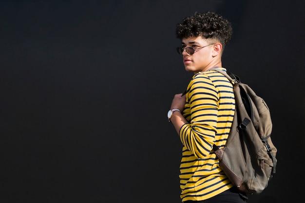 Junger ethnischer mann in der sonnenbrille mit rucksack gegen schwarzen hintergrund Kostenlose Fotos