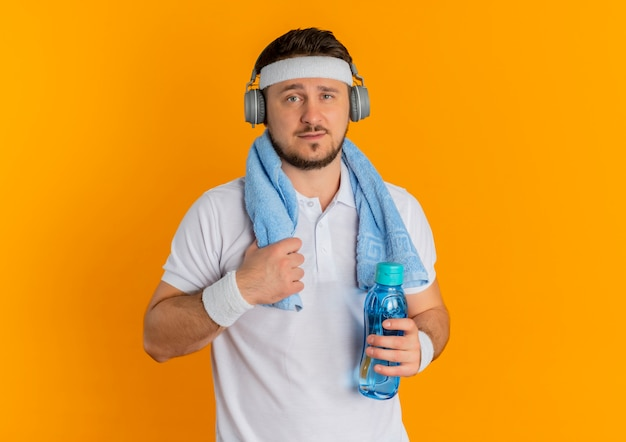 Junger fitness-mann im weißen hemd mit dem stirnband und dem handtuch um den hals, der flasche wasser hält, die kamera mit dem sicheren ausdruck steht, der über orange hintergrund steht Kostenlose Fotos