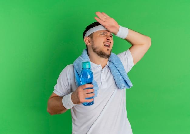 Junger fitness-mann im weißen hemd mit stirnband und handtuch um seinen hals, der flasche wasser müde und erschöpft nach dem training steht über grünem hintergrund hält Kostenlose Fotos