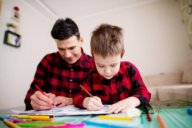 Junger fokussierter vater und sohn im gleichen roten hemd, das mit einem bunten satz von stiften malt, während sie am tisch in einem hellen wohnzimmer sitzen. Premium Fotos
