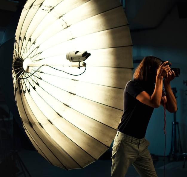 Junger fotograf, der vor einem reflektierenden regenschirm steht Premium Fotos