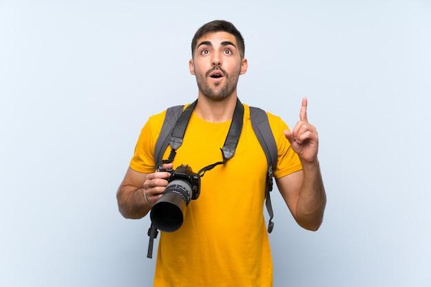 Junger fotografmann, der mit dem zeigefinger eine großartige idee zeigt Premium Fotos