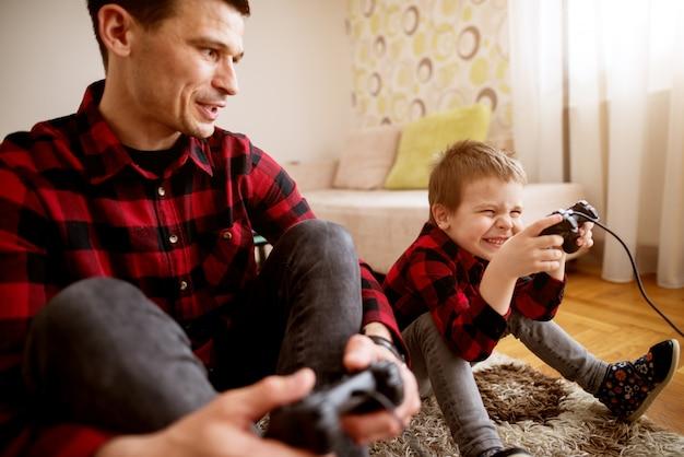 Junger fröhlicher aufgeregter vater und sohn im gleichen roten hemd, die konsolenspiele mit gamepads in einem hellen wohnzimmer spielen. Premium Fotos