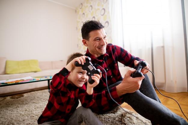 Junger fröhlicher aufgeregter vater und sohn im gleichen roten hemd, die konsolenspiele mit gamepads spielen, während sie sich in einem hellen wohnzimmer aneinander lehnen. Premium Fotos