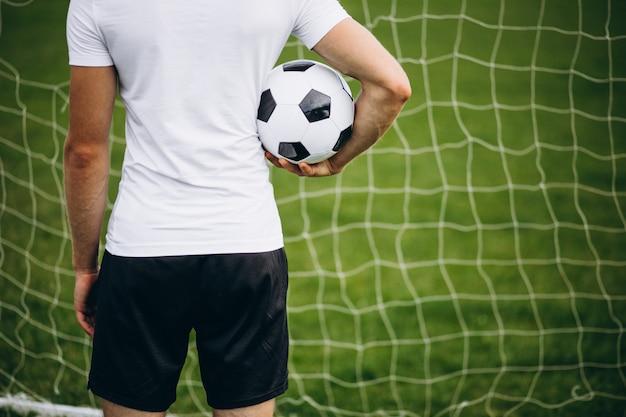 Junger fußballspieler am fußballplatz Kostenlose Fotos