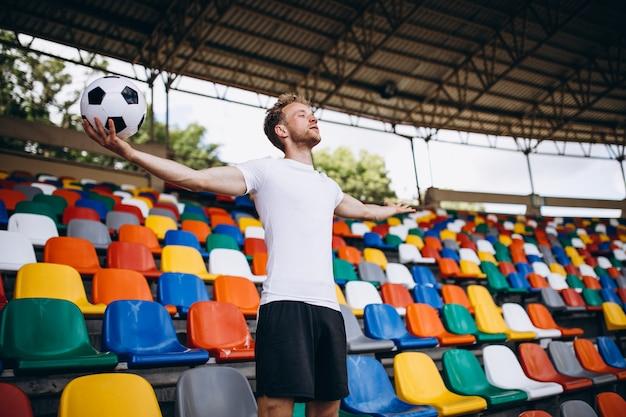 Junger fußballspieler an den tribünen das spiel aufpassend Kostenlose Fotos